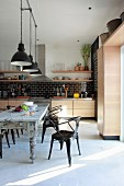 Retro metal chairs at shabby chic dining table and industrial pendant lamps with black and white lampshades in designer kitchen