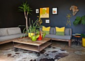 Plants in bright pots on rustic coffee table on castors in front of couches with seat cushions against black walls