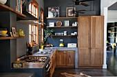 Gemauerte Küchenzeile und Massivholz Schrankfronten in offener Küche mit schwarz getönter Wand
