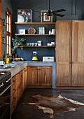 Masonry kitchen counters with solid wooden doors in open-plan kitchen with black-painted wall and animal-skin rug on polished concrete floor