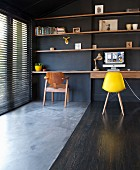 Classic yellow shell chair at minimalist desk below wooden shelves on black-painted wall; polished concrete and wooden floor