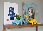Planters shaped like miniature dinosaurs and pictures on wooden shelf