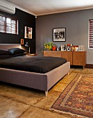 Double bed with grey upholstered frame and black bed linen in dark-painted master bedroom