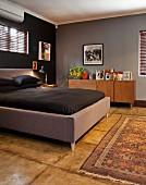 Doppelbett mit gepolstertem Rahmen in Grau und schwarze Bettwäsche in dunkel getöntem Elternschlafzimmer
