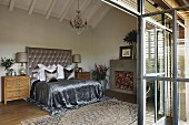Spacious attic bedroom; shimmering silver throw on double bed with tall, button-tufted headboard against wall