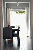 Dining area with rustic table lit from behind by open French windows leading to garden