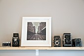 Black and white cityscape flanked by collection of old cameras on wall-mounted shelf