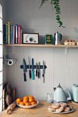 Still-life arrangement in corner of kitchen with cookery books, radio and kitchen utensils on shelf above magnetic knife rack