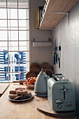 Vintage-style toaster and kettle on kitchen worksurface in front of window with view of maritime anchor motif
