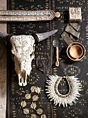 African jewellery, home accessories made from natural materials and animal skull on dark runner with small graphic pattern