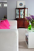 White sofa with pink scatter cushions and plastic side table; antique display cabinet against wall in background