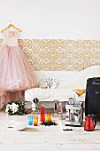 Wedding present ideas - espresso machine and colourful glasses on wooden floor in front of vintage chaise longue next to wedding dress hanging from coathanger on wall