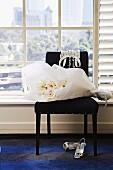 Weisser Blumenstrauss im Papier auf schwarzem, gepolstertem Stuhl und Damen Pumps auf Teppich vor Sprossenfenster