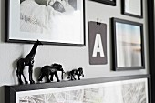 Gallery of pictures with tiny, black animal figurines on picture frame
