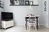 Dining area with vintage chairs and metal locker on castors used as TV cabinet below gallery of black and white pictures
