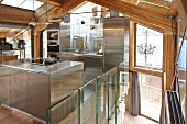 Designer, stainless steel, fitted kitchen in modern chalet with exposed wooden roof structure and glass walls