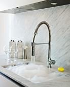 Küchenzeile mit Arbeitsbereich aus hellgrauen Marmorplatten, Armatur mit Schlauchbrause und Spülbecken mit schäumendem Wasser