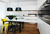 White fitted kitchen with marble worksurfaces and table top and yellow and black chairs