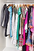 Women's clothing on hangers on rail in open wardrobe