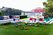 White outdoor furniture with red, white and blue accessories in front of pool; croquet set in foreground on lawn in luxurious gardens