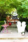 Verschiedene Outdoor Möbel auf podestartigen Stufen im Garten - verspiegelte Kugel auf Boden vor weißem Kunststoff Sessel und Tisch mit Obstschale, dahinter Rattan Sessel mit passendem Schemel