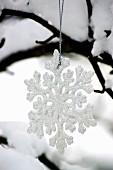 Eiskristall-Anhänger am schneebedeckten Baum