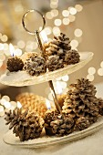Pine cones and candles on cake stand