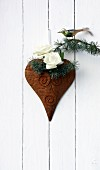 Two white roses and cedar twig with bird figurine on heart ornament on wall