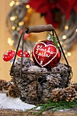 Basket of pine cones and red Christmas bauble with fly agaric ornaments in background