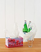 Empty tissue box used to store plastic bags; two bottles of mineral water in plastic bag on wooden table