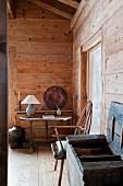 Offene Holztruhe neben Stuhl, im Hintergrund schlichter Tisch mit Tischlampe im Wohnzimmer einer Hütte