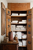 Open, rustic, wooden linen closet built into niche