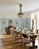 Chandelier above festively set dining table and upholstered, antique wooden chairs in country-style dining room with old herringbone parquet floor
