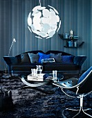 Wohnzimmer in Blau - Couchtisch mit geschwungenem Fussgestell und Sofa vor Wand in Streifenoptik unter kugelförmiger Hängeleuchte; im Vordergrund Drehsessel