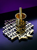 Brass mortar and pestle on trivet formed from connected lettering surrounded by violet surfaces