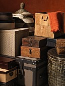 Stacked storage containers made from various materials such as wicker, wood, cardboard and leather crammed together in small space