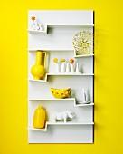 Weisses Hängeboard mit Deko-Objekten auf Zickzack-Fächern an gelber Wand