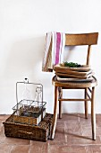 Wooden dishes stacked on wooden chair against white wall; bottle carrier standing on wicker case