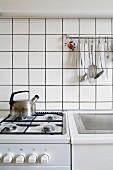 Gasherd mit Wasserkessel neben geriffelter Abtropffläche eines Spülbeckens, darüber Edelstahlstange mit Küchenutensilien