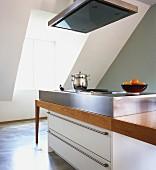 Kochinsel mit weißem Schubladenschrank und Edelstahlaufsatz in einer Dachwohnung
