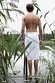 Junger Mann mit Handtuch um die Hüfte steht auf einem Steg am See