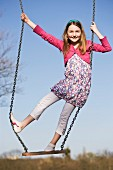 A girl standing on a swing
