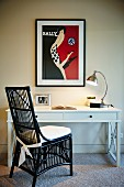 Black painted wicker chair at white desk with lamp below poster on wall