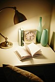 Open book below lamp on desk with clock and vases