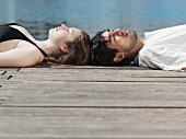 A young couple lying on a jetty head to head
