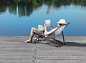 A young man sitting in a deck chair on a jetty reading a book