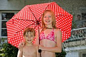 Two children standing under an umbrella in their bathing suits