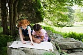 Two young girls reading a map outdoors