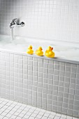 A bubble bath with rubber ducks on side of tub