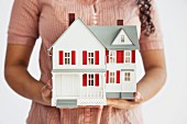 Midsection of a woman holding a miniature house